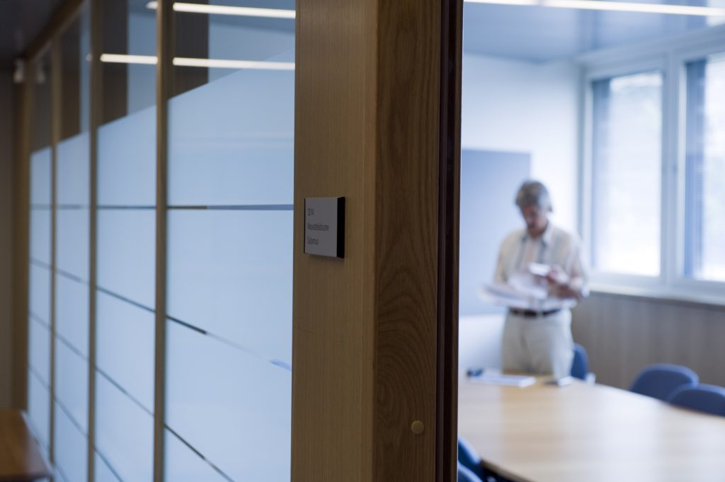 Kokoustilan ovelta näkyy mies kokouspöydän äärellä.