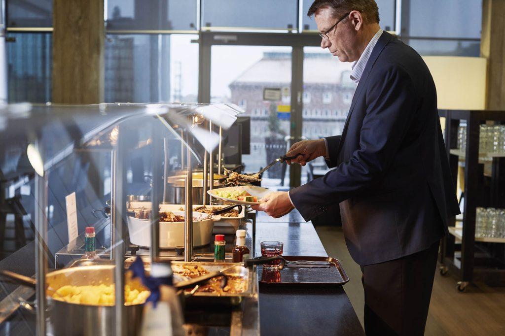 mies ruokalan linjastolla ottamassa ruokaa.