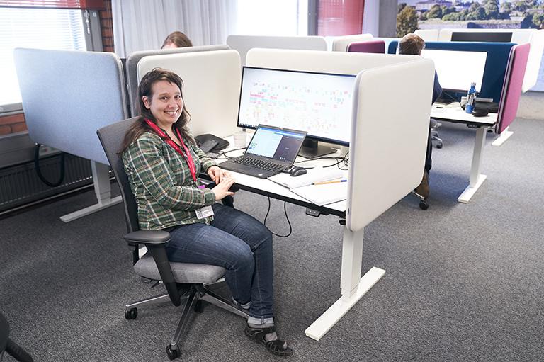nainen monitilan työpisteellä edessään läppäri ja iso näyttö