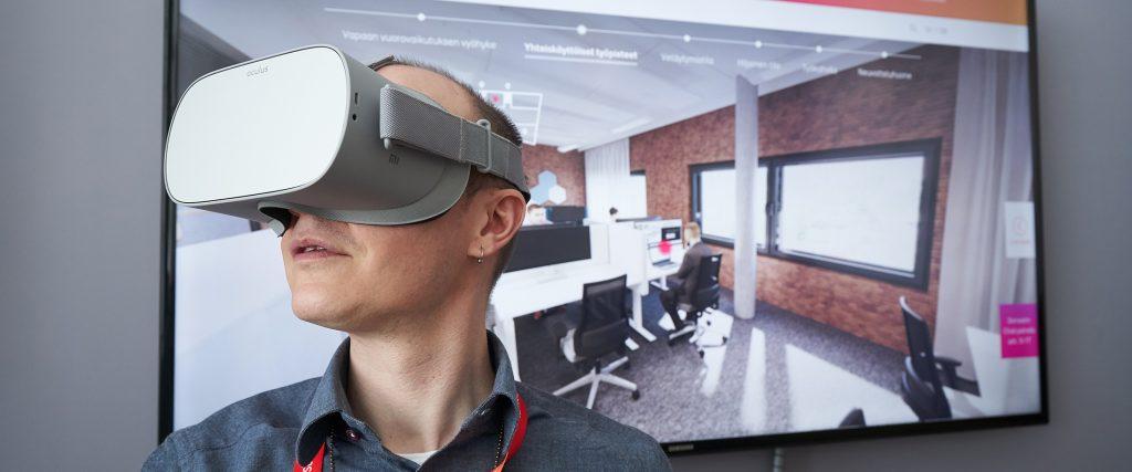 Mies virtuaalilasit päässä, taustalla näytöllä virtuaaliesitys toimistotilasta.