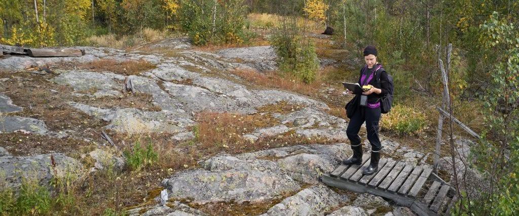 Nainen seisoo kalliolla kädessään karttoja ja paikanninlaite.