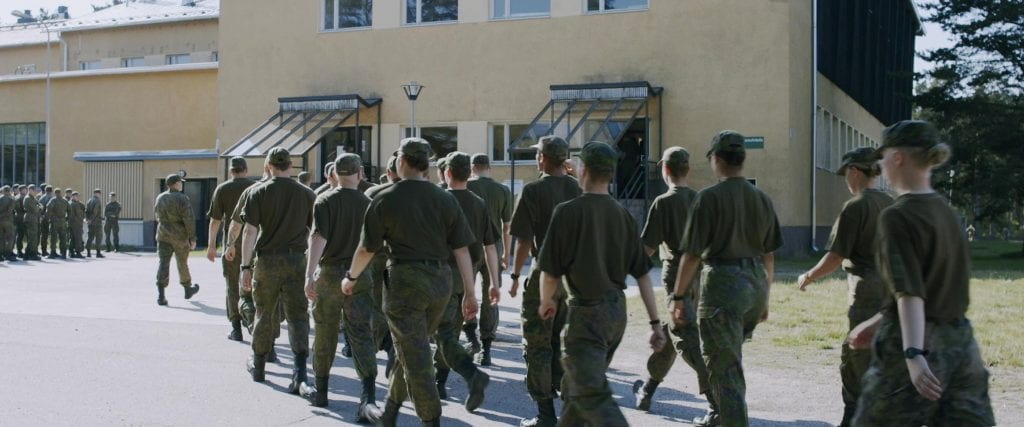 Varuskuntaan marssivia miehiä ja naisia.